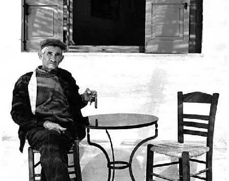 懒洋洋地坐在传统希腊咖啡屋小椅子上的老一代希腊人